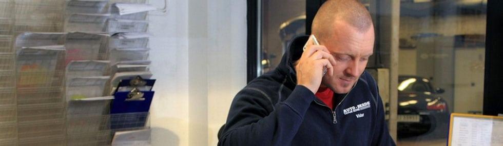 Ansatt på Auto-Skade prater i telefonen
