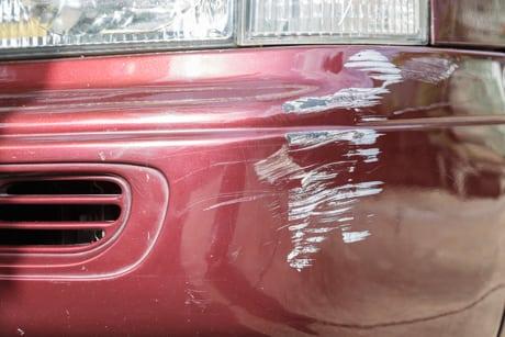 Riper i lakken på rød bil